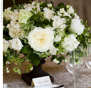 Low pedestal vases filled with fluffy hydrangeas and garden roses topped some of the tables at the reception.