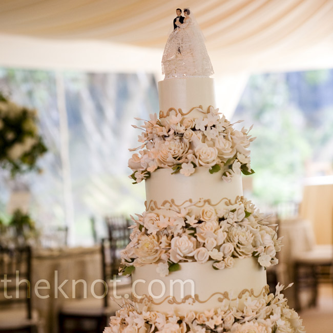 Gold piping and layers of intricate sugar flowers were extra-elegant touches. The couple finished it off with a vintage cake topper.