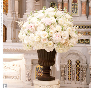 Two lush, all-white floral arrangements in pedestal vases marked the altar.
