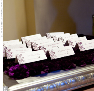 Boxes of tightly packed purple carnations served as a base for the escort cards.