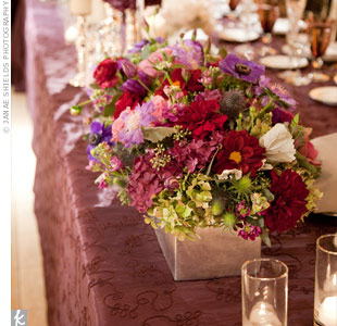 Groupings of candlesticks topped with pillar candles and purple hydrangea balls separated the oversized flower arrangements on the long banquet tables.