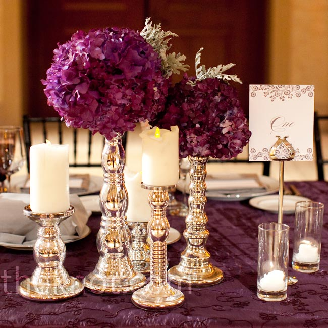 Groupings of candlesticks topped with pillar candles and purple hydrangea balls topped the banquet tables.
