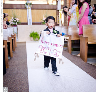 "Kimberly's nephew carried a ""Here Comes the Bride"" sign down the aisle."