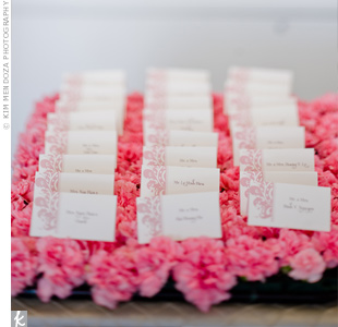 The pink escort cards were displayed atop a bed of fresh, pink carnations.