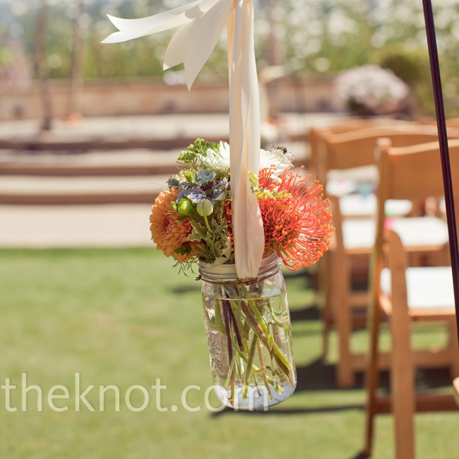 Simple mason jar flower arrangements hung from shepherd's hooks at both ends of the grassy aisle.
