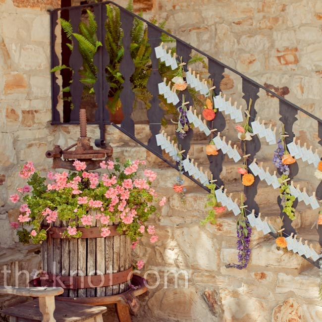 White escort cards and flowers were strung along the ranch's stone staircase.