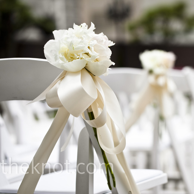 Simple arrangements of a few ribbon-tied peonies marked the rows of chairs.