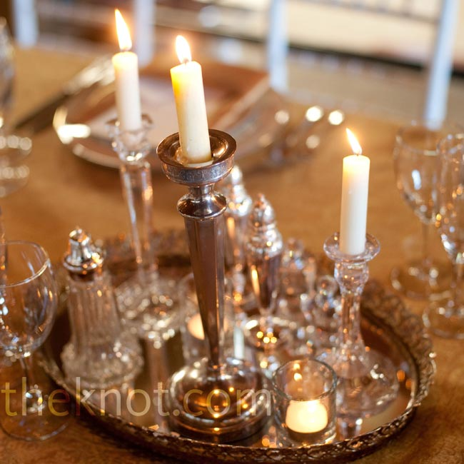 An eclectic mix of silver and glass candlesticks atop mirrored trays offset the floral centerpieces.