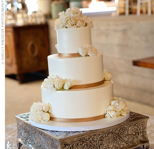 Fresh white peonies and gold ribbon decorated the buttercream cake for an elegant look.