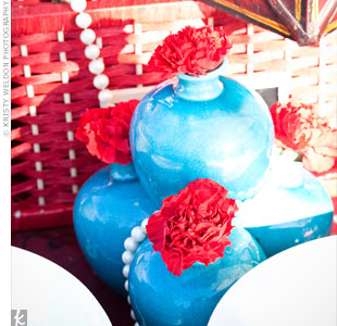 Bright turquoise vases filled with red carnations added lots of color to the tables.