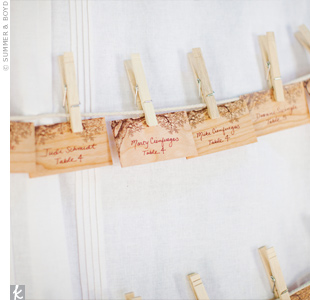 The simple, wooden escort cards hung along a length of twine with clothespins.