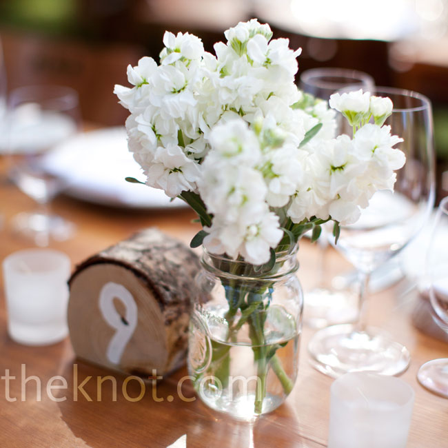 Mason jars filled with all-white flowers were sprinkled on all of the dinner tables to achieve a country-home vibe.