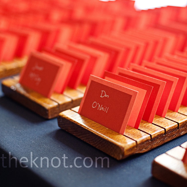 Katie's uncle made slits into wooden blocks to hold the escort cards, printed on paper in shades of red.