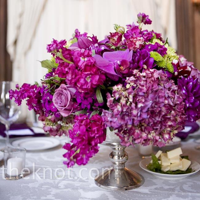 Silver urns filled with a mix of magenta flowers (like hydrangeas, roses and orchids) topped the tables.