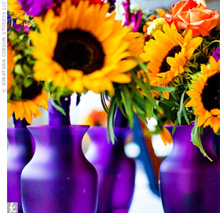 Laura and her bridesmaids assembled their own bouquets with the florist's guidance. At the reception, the flowers decorated the cake table in purple vases.