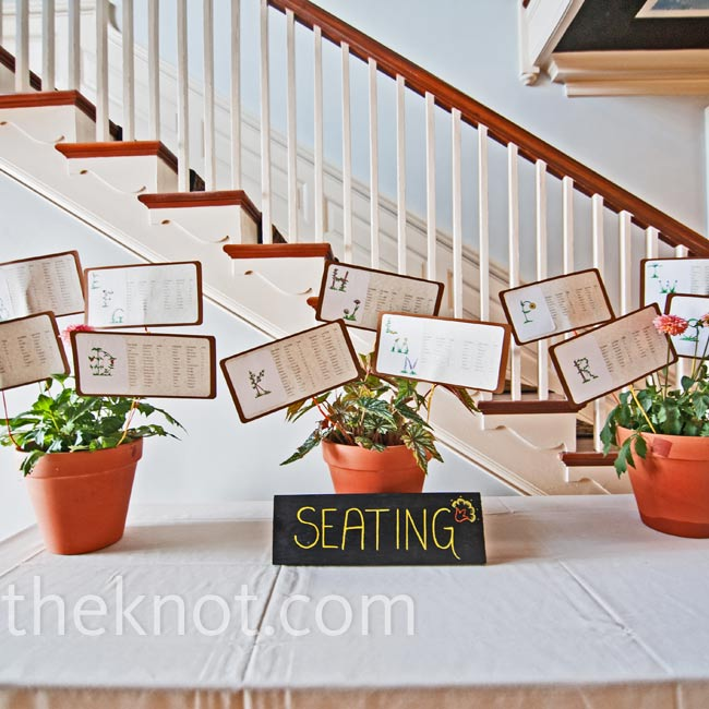 Nat made cards listing the guests' names and table numbers, and planted them into potted dahlias.