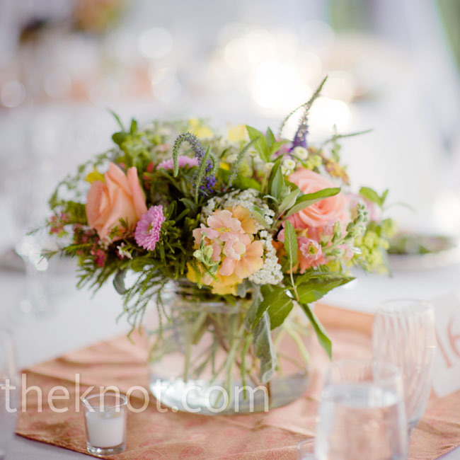 Local, seasonal flowers arranged loosely in a mix of vases and jars made for environmentally friendly and pretty table décor.