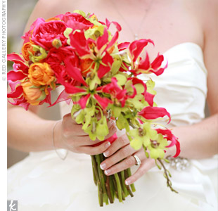 Annes striking bouquet was made of cascading gloriosa lilies, orange ranunculus and green dendrobium orchids.