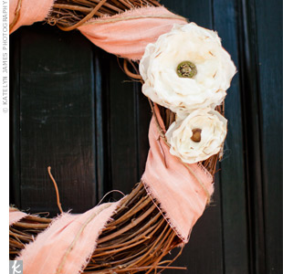 Twig wreaths wrapped in peach fabric and accented with white fabric flowers decorated the doors of the chapel.