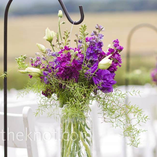 The aisle was lined with Mason jars of purple flowers hanging from shepherd's hooks.