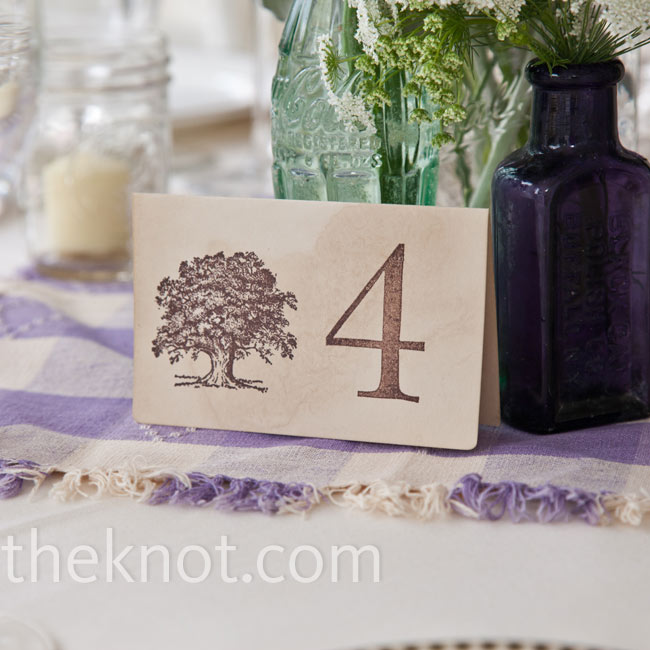 Coffee-stained card stock was stamped with the table number and the same tree motif from the invitations.