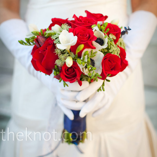 The red and white bouquet was wrapped in blue fabric and filled with roses, anemones, freesia and eucalyptus.