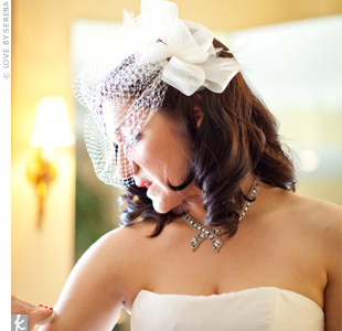 A birdcage veil with ribbon and feather details added a touch of old Hollywood glamour to Shannon's look.
