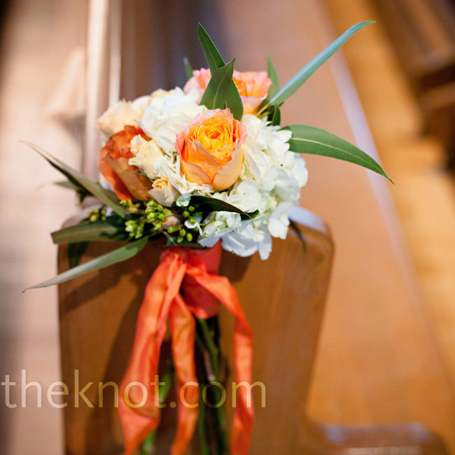 Coral roses were grouped with white hydrangeas, greenery and coral ribbon and placed on the pews lining the aisle.