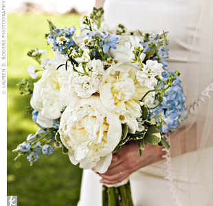 Blue hydrangeas and delphinium added a touch of color to a lace-wrapped bouquet of white peonies and roses.