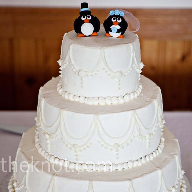 The white buttercream was decorated with a simple design of scallops and dots. Bride and groom penguins, complete with top hat and veil, were perched on top.