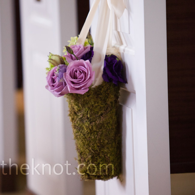 Suspended by ivory ribbon, purple flowers in moss-covered containers decorated every other pew along the aisle.