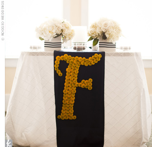 "The florist surprised the couple by hanging a banner of yellow button mums arranged in the shape of an ""F""  from the table."