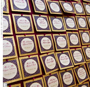 Purple and gold glittered escort cards were displayed on a fabric-covered board.