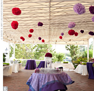 Purple and red paper poms hanging from the rafters and sequin linens set the tone for the evening's party.