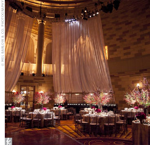 Dramatic draping, warm uplighting and a mix of high and low centerpieces created a romantic vibe at the reception.