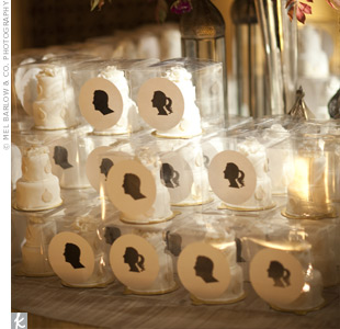 Guests took home mini wedding cakes set inside clear boxes with stickers of the couples silhouettes.