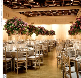 White draping around the perimeter of the ballroom created a romantic atmosphere, while silver pleated organza linens and overflowing lilac centerpieces enhanced the vibe.