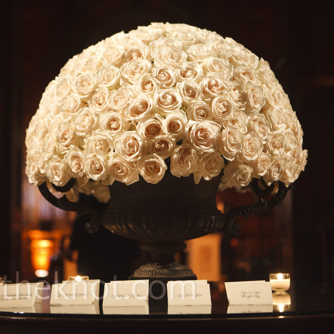 An eye-catching pavé arrangement of white roses served as the focal point of the escort card table.