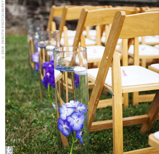 Tall cylinder vases of submerged purple orchids and floating votives 
