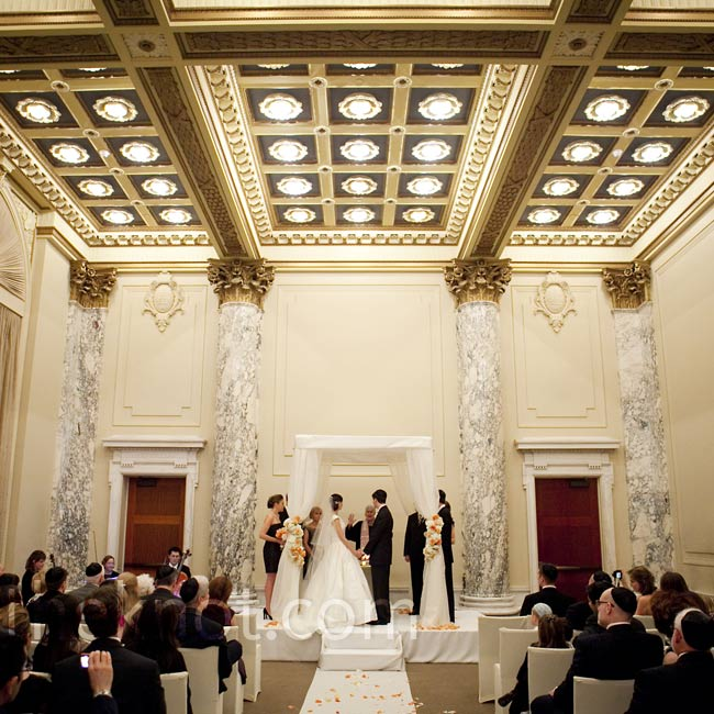The couple loved the ballroom's stunning architecture, so they added only a white aisle runner and white-draped huppah.