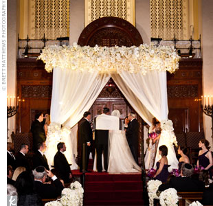 Dramatic white draping, and orchids, hydrangeas and roses made up Stephanie and Joshs ethereal huppah.