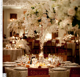 Tall, glass, trumpet-style vases overflowing with white and ivory orchids, hydrangeas and roses topped the tables, matching the gold linens.