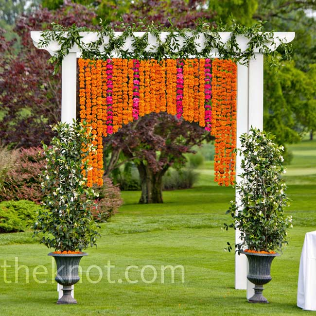 Strings of orange marigolds and hot pink carnations hung from the white ceremony arbor.