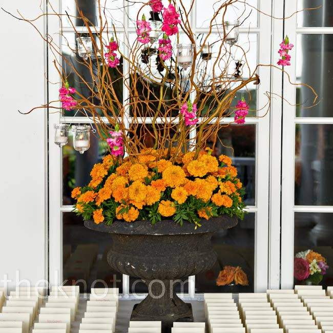 Marigolds, curly willow and hanging votives marked the escort card table.