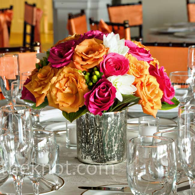 Bright arrangements of roses, dahlias and hypericum berries filled low silver vases.