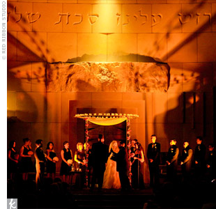 Warm lighting illuminated the ceremony space, where the round Lucite huppah was covered in candles 