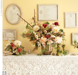 As guests enter the reception, a grand escort card wall takes center stage. The intricate lace tablecloth dresses up a collection of shabby-chic frames displaying guests' seating arrangements.