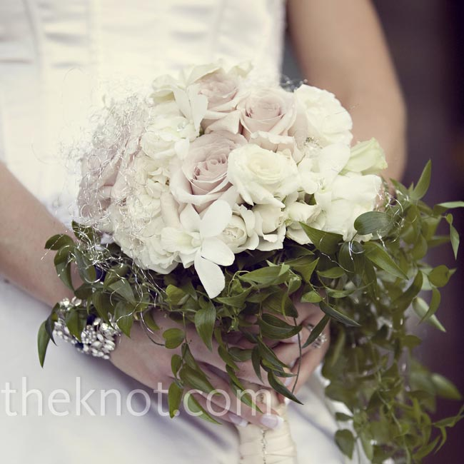All Ali requested for her bouquet was a romantic cascade with her family rosary attached. Her florist used a mix of champagne roses, ivory spray roses, white lisianthus, greens and silver angel hair.