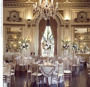 Metallic linens and gold chiavari chairs blended with the ballrooms warm tones, bringing the focus to the tall, dramatic centerpieces.