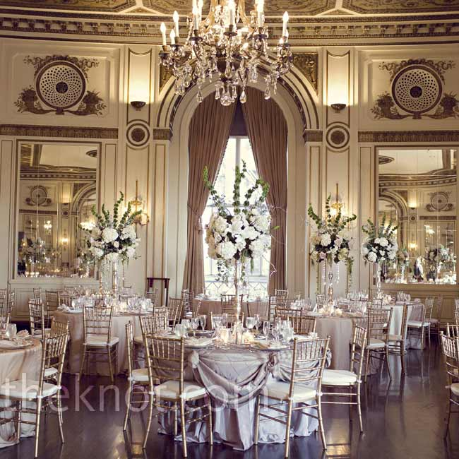 Metallic linens and gold chiavari chairs blended with the ballroom's warm tones, bringing the focus to the tall, dramatic centerpieces.